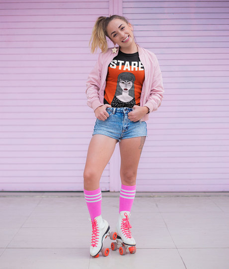 Mockup of a trendy woman wearing a t shirt and roller skates against a pink metal curtain a18557